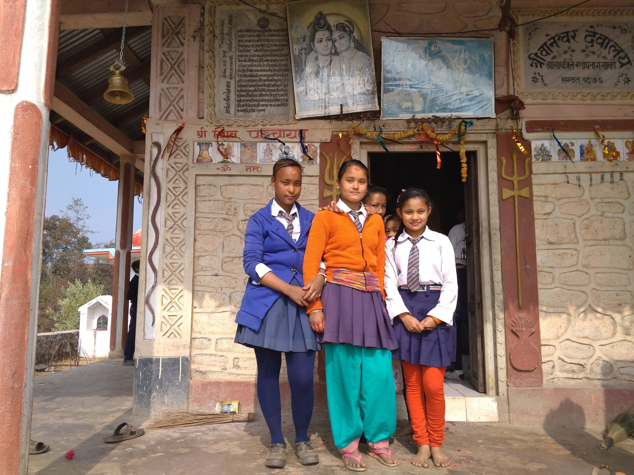 Three girls stand outside temple in school uniform.