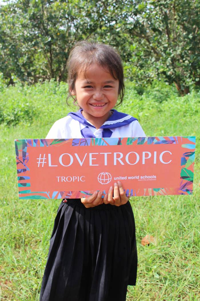 Cambodia student with Love Tropic banner